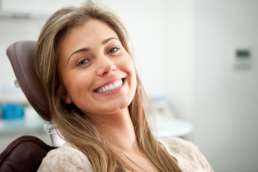 Woman sitting in a dentist chair and smiling